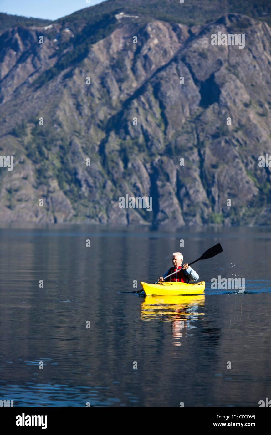 Un homme à la retraite aventureux kayak à travers un immense lac calme dans l'Idaho. Photo Stock