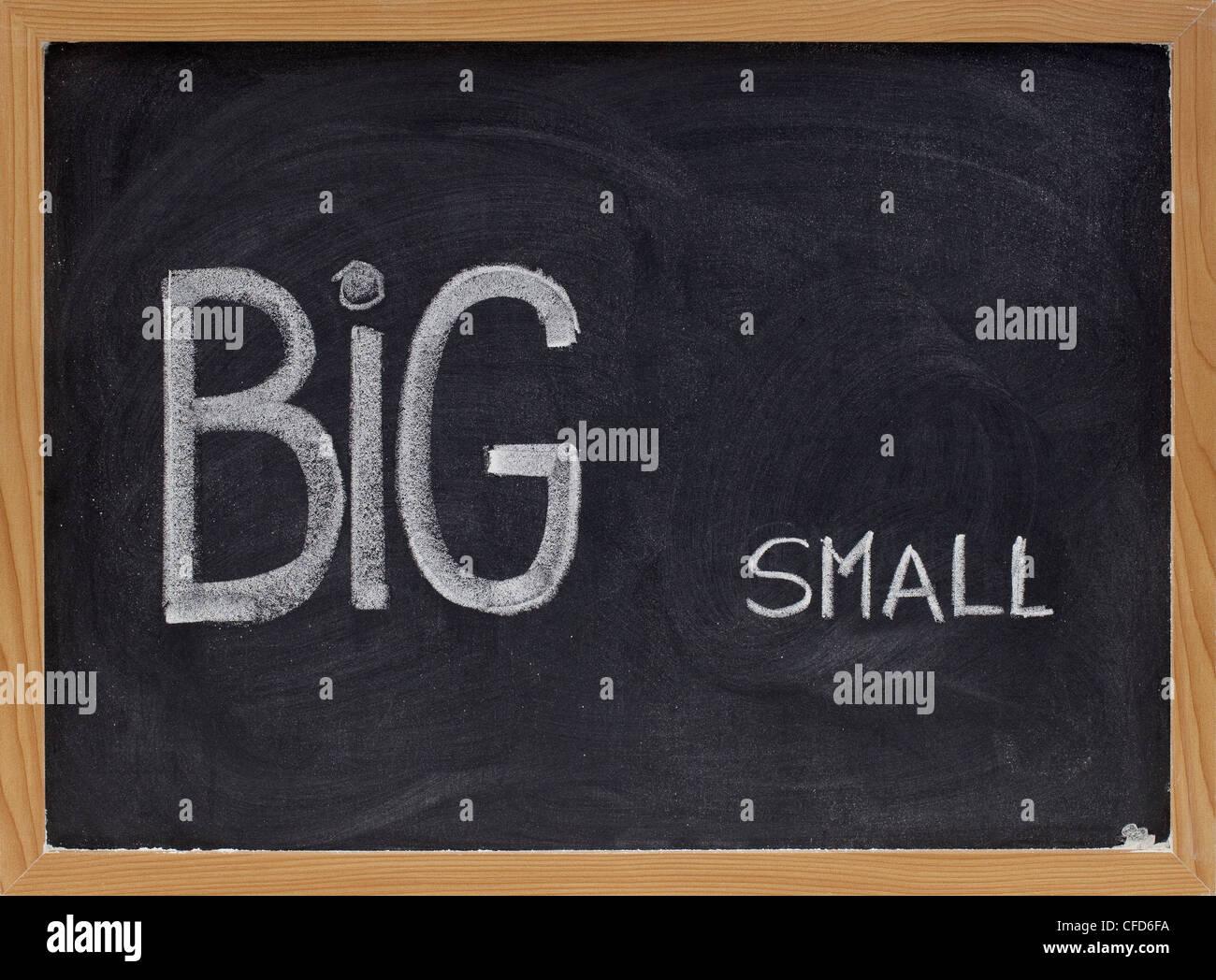 Mots écrits à la main, petits et grands avec craie blanche sur tableau noir, le contraste, le concept Photo Stock