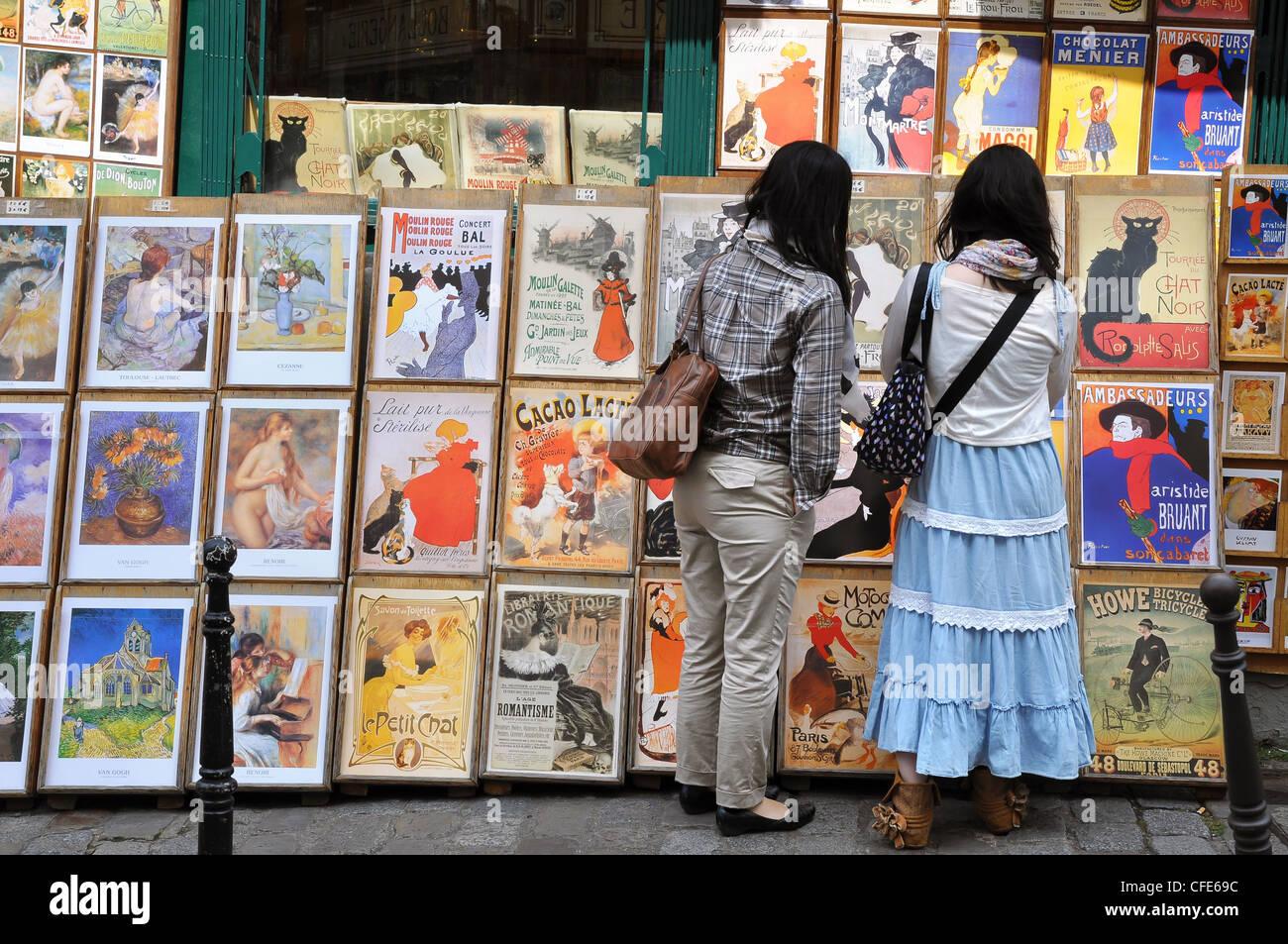 Deux femmes asiatiques touristes parcourt des souvenirs dans un art stall à Montmartre, paris. Banque D'Images