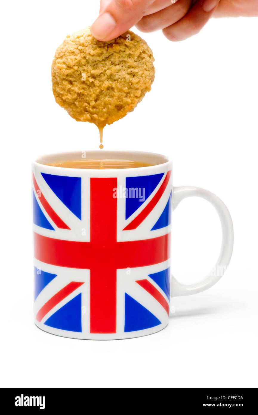 Biscuit tremper dans la tasse de thé tourné en studio sur fond blanc. Banque D'Images