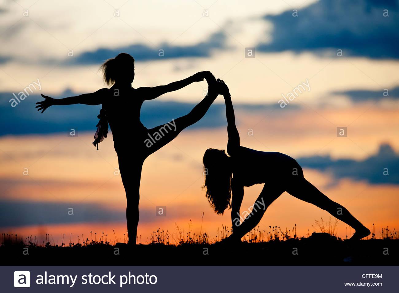 Deux femmes effectuer le yoga sur le sommet d'une montagne. Photo Stock