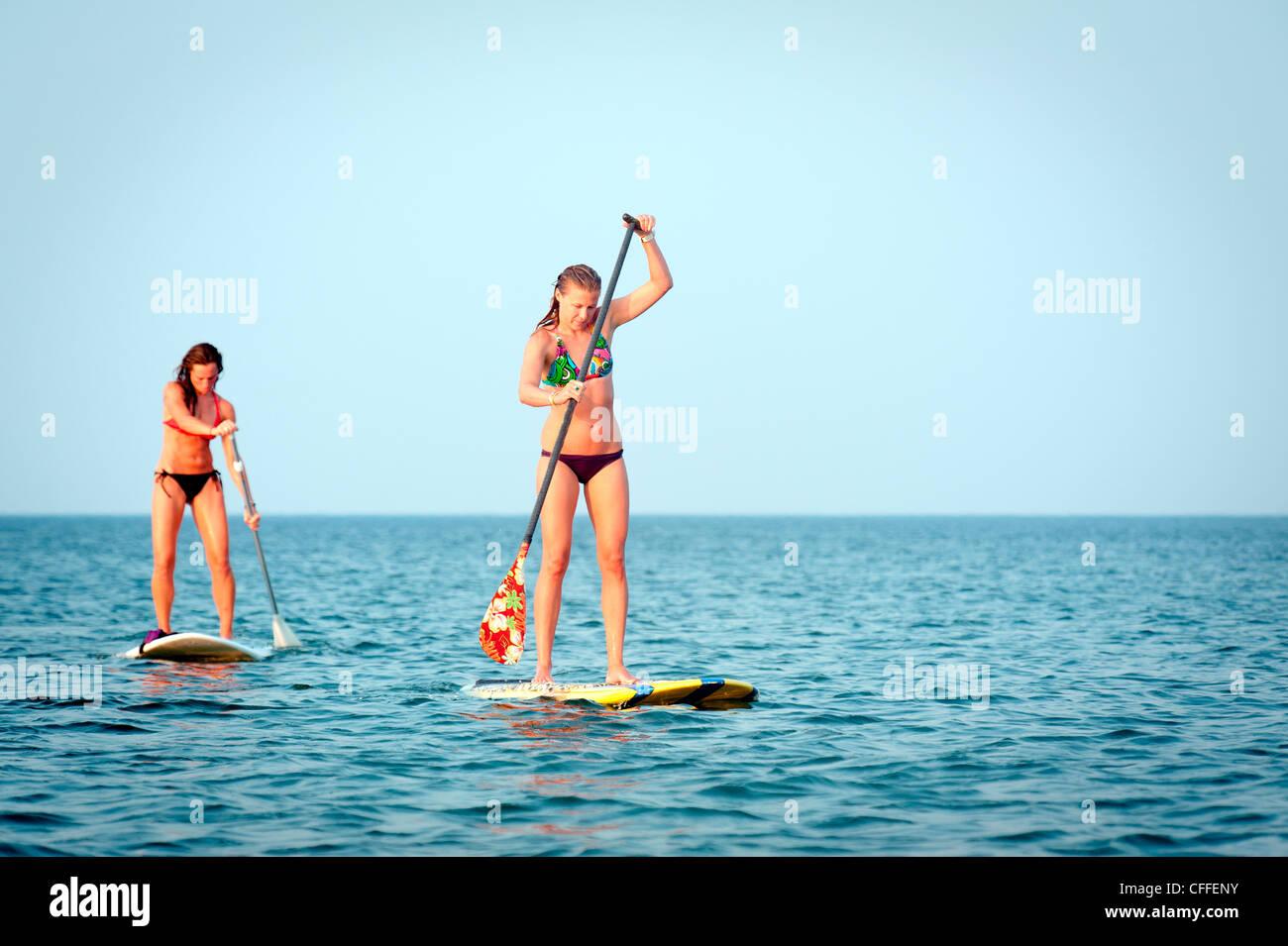 Deux femmes stand up paddle board par la côte. Photo Stock