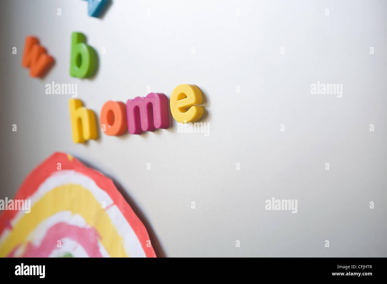 L'orthographe des lettres sur 'Accueil' famille réfrigérateur Photo Stock