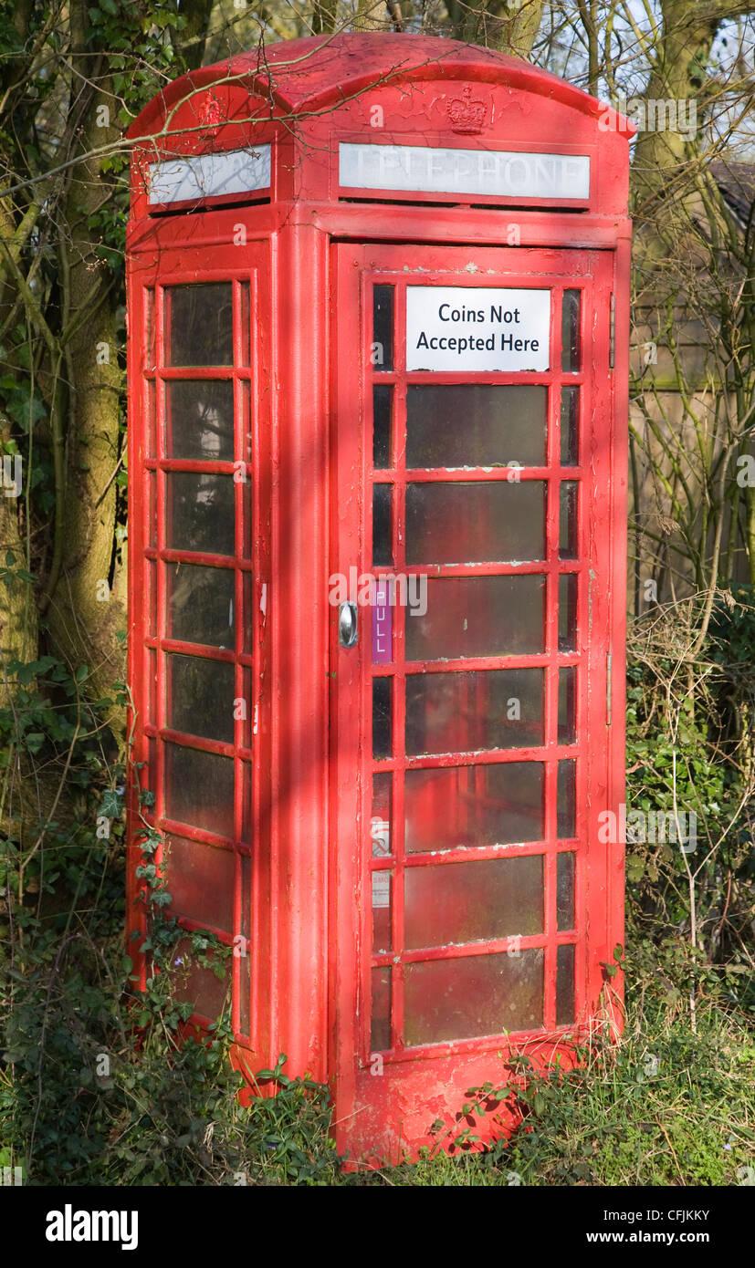 Boîte de téléphone rouge traditionnel en zone rurale avec panneau disant pièces qui ne sont Photo Stock