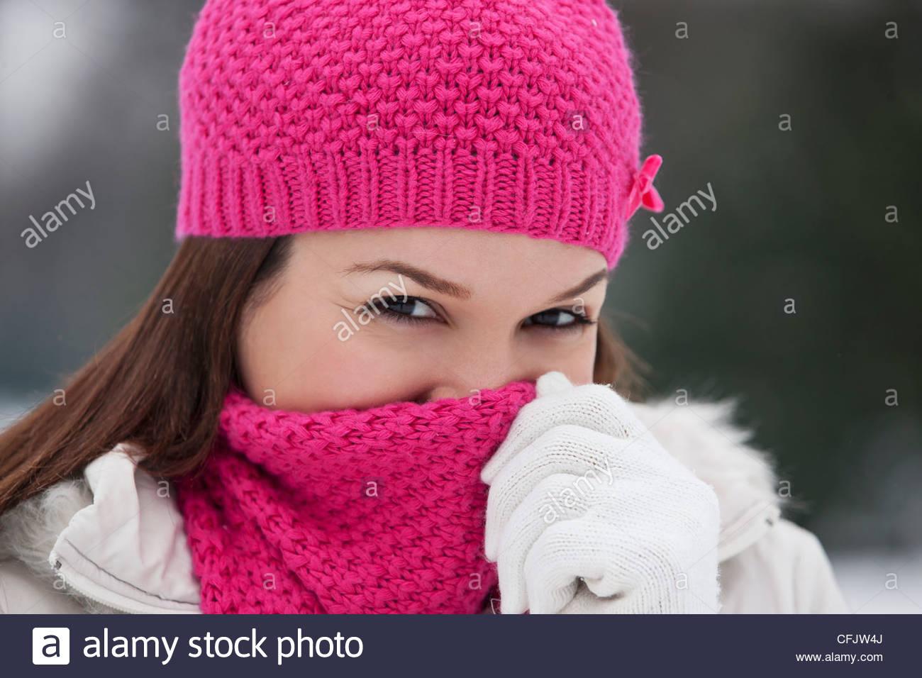Une jeune femme portant un chapeau et un foulard rose, en essayant de garder au chaud Photo Stock