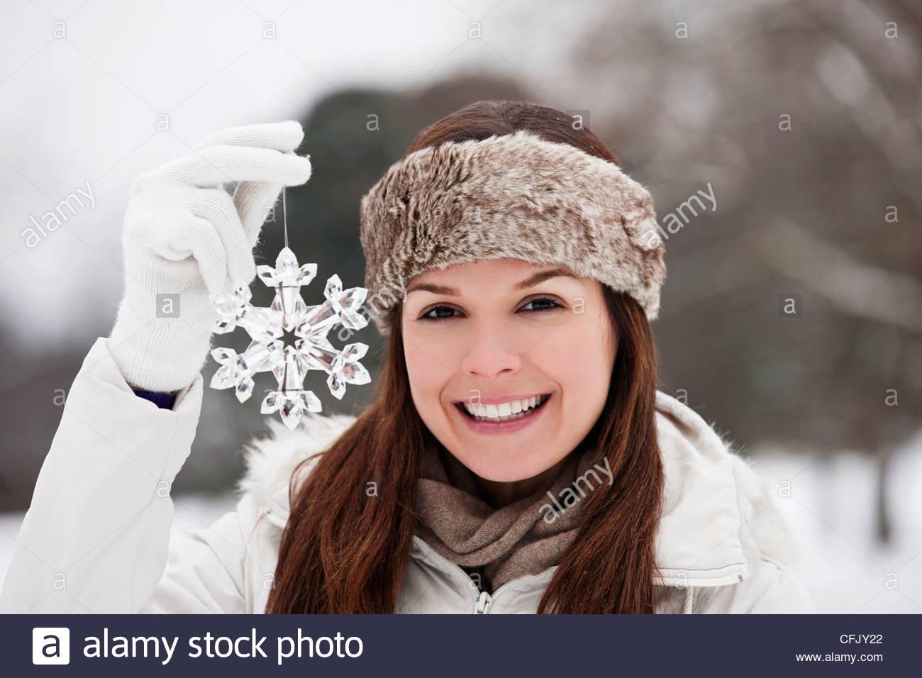 Une jeune femme tenant une décoration flocon Photo Stock