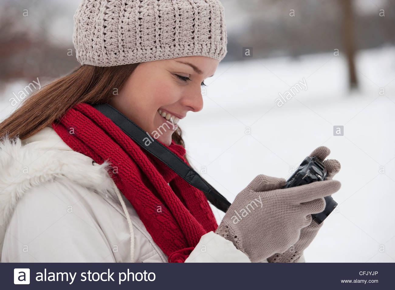 Une jeune femme debout dans la neige, à la recherche de son appareil photo Photo Stock