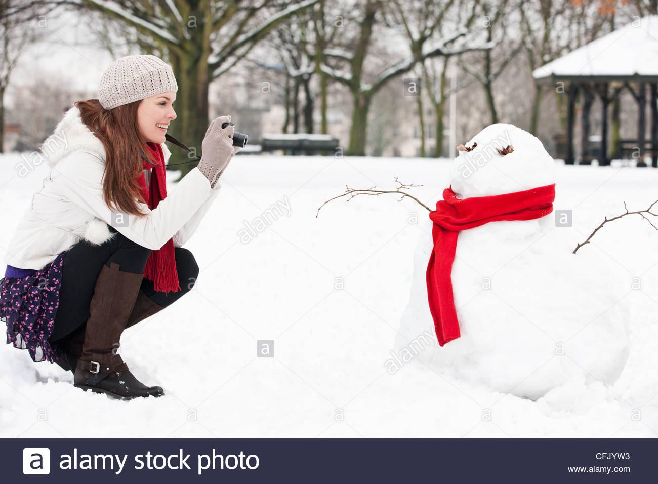Une jeune femme de prendre une photo d'un bonhomme de neige Photo Stock