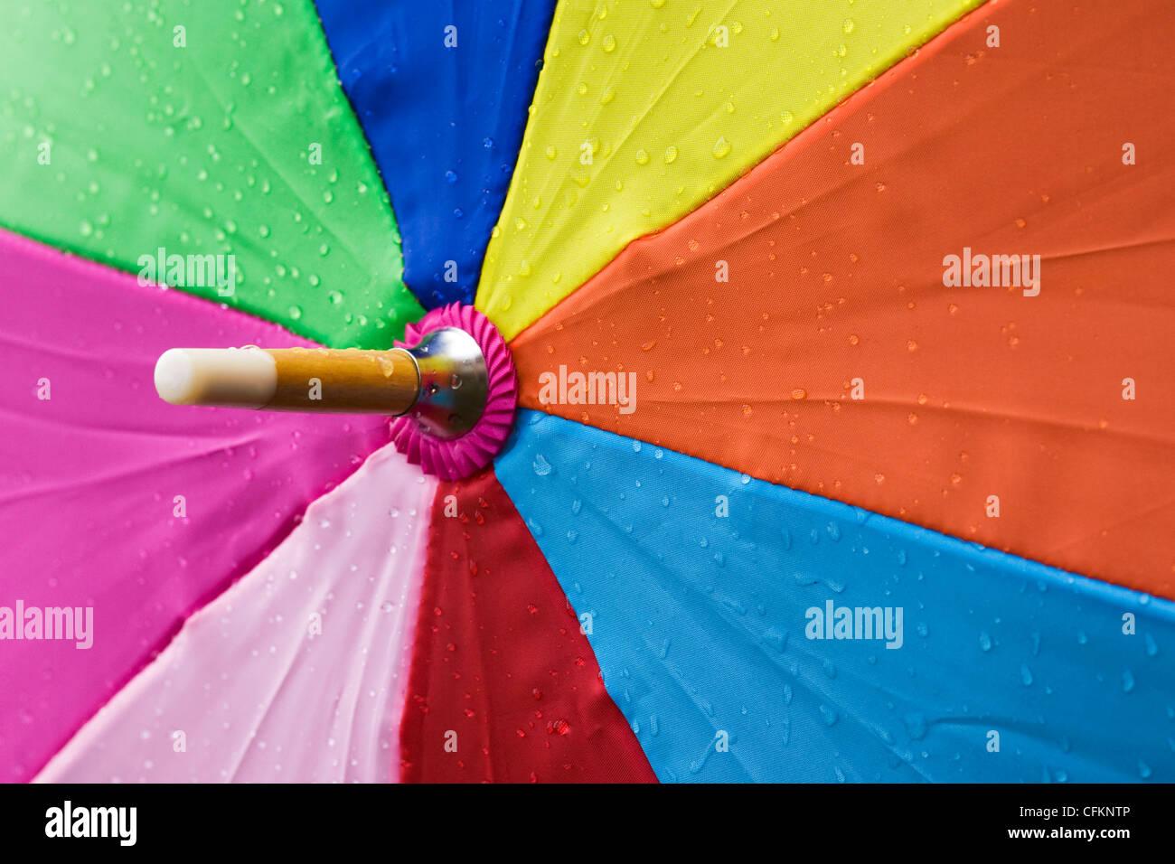 Close up d'un parapluie multicolore sous la pluie. Photo Stock