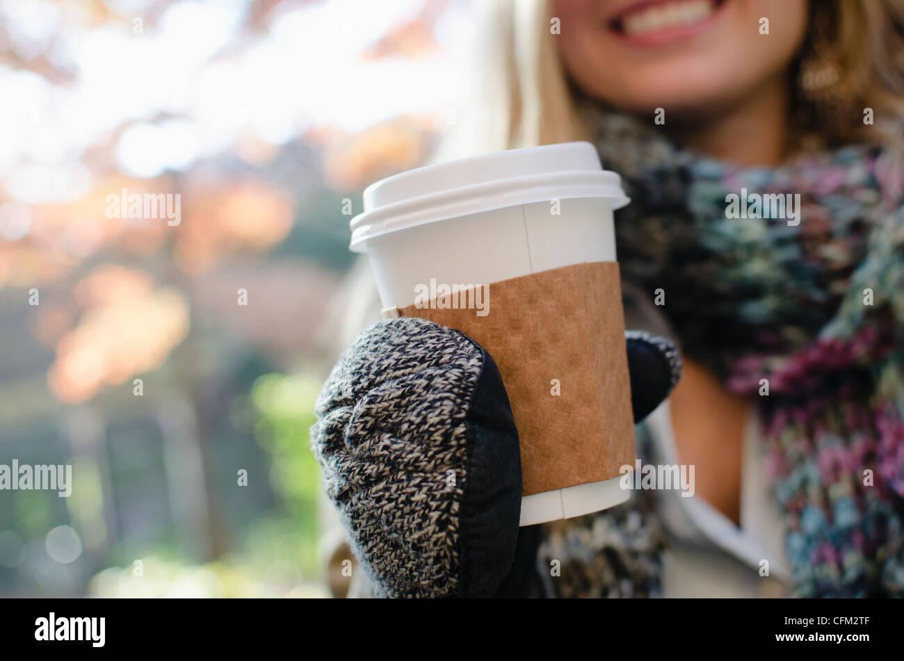 USA, l'État de New York, New York City, Brooklyn, Femme portant des gants holding Coffee cup Banque D'Images