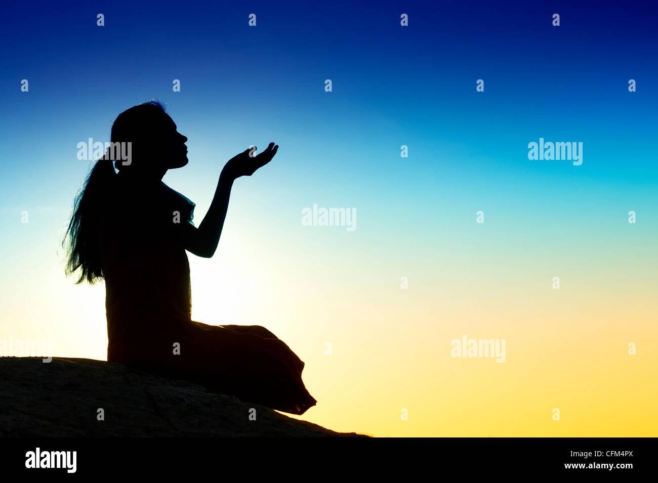 Indian girl offrant ses prières avec ses mains en l'air. Silhouette. L'Inde Photo Stock