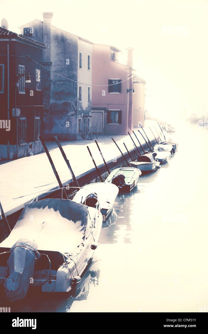 Bateaux dans le soleil sur un canal à Burano, Venise, Italie Photo Stock