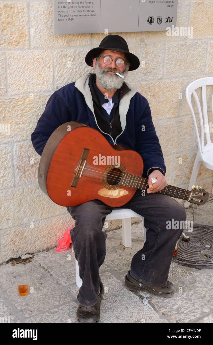 Guitariste aux spectacles de rue dans la vieille ville de Jérusalem, Israël bénéficie d'une pause cigarette. Banque D'Images