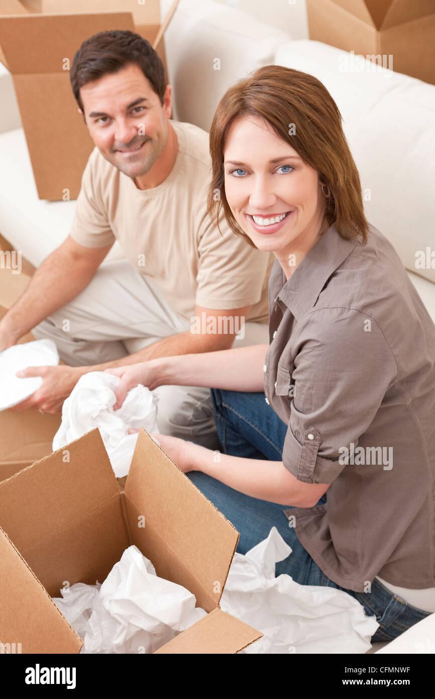 Heureux couple dans la trentaine de déballer ou boîtes d'emballage et de déménagement dans une nouvelle maison. Banque D'Images