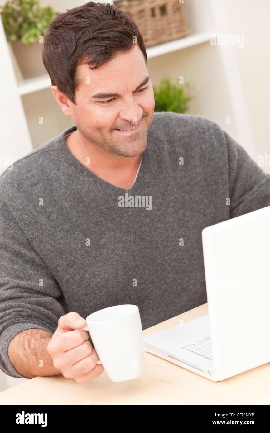 Couple dans la trentaine à la maison en utilisant son ordinateur portable de boire du thé ou du café Photo Stock