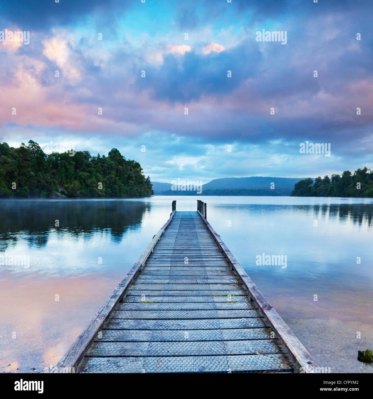 Jetée au lac Mapourika, sur la côte ouest de l'île Sud de la Nouvelle-Zélande, à l'aube. Photo Stock
