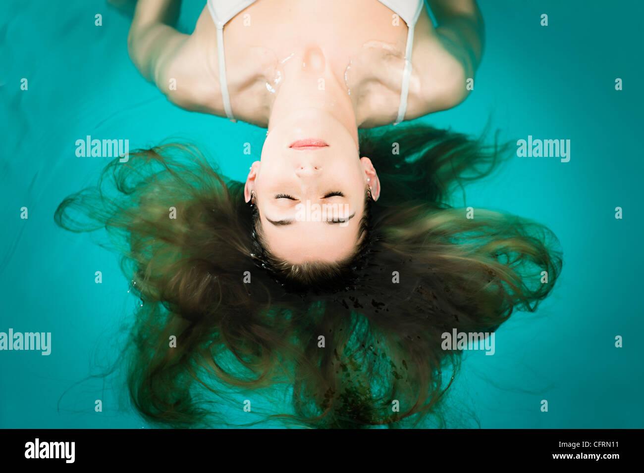 Bien-être - jeune femme flottant dans un spa ou une piscine, elle est très détendue Photo Stock