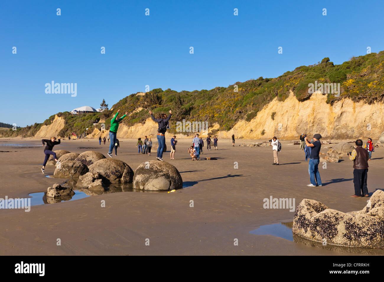Les touristes à poser et prendre des photos à Moeraki Boulders à marée basse, Otago, Nouvelle-Zélande. Banque D'Images