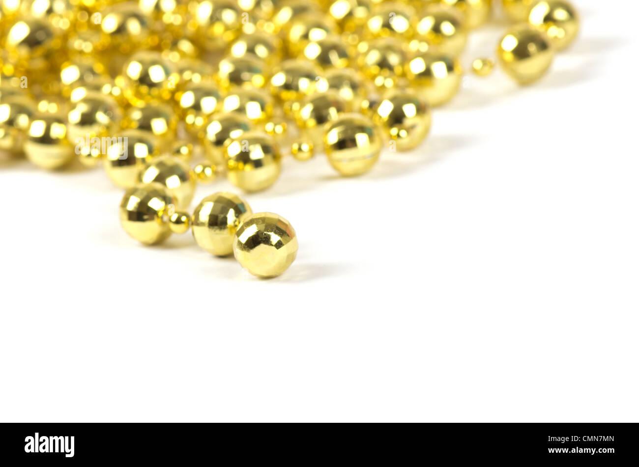 A l'arrière-plan d'une brillante couleur or perles de célébration d'over white Photo Stock