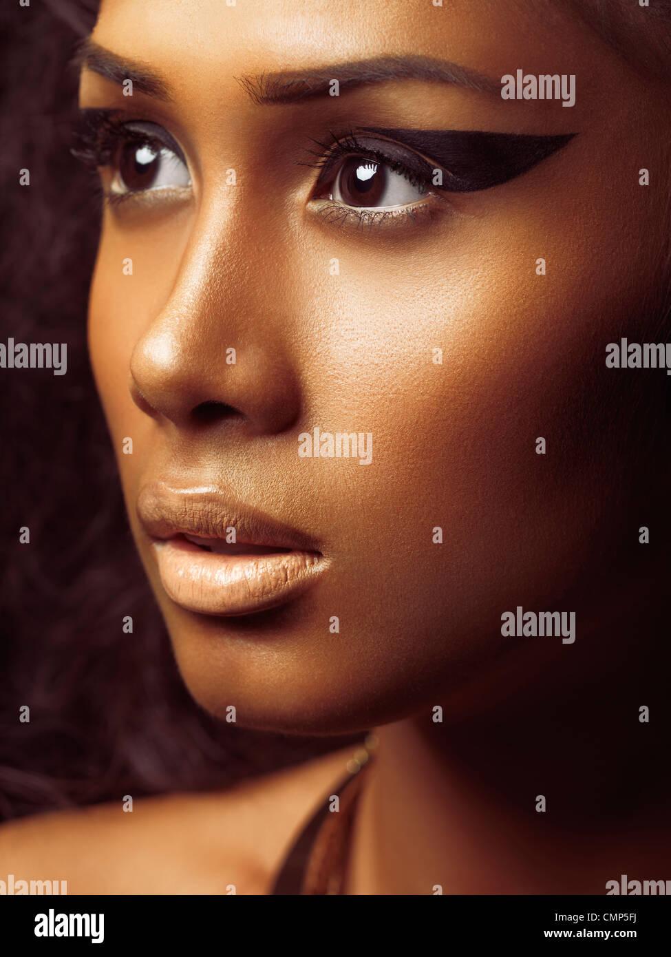 Beauté exotique closeup portrait of a young woman's face avec la peau dorée et le maquillage artistique Photo Stock