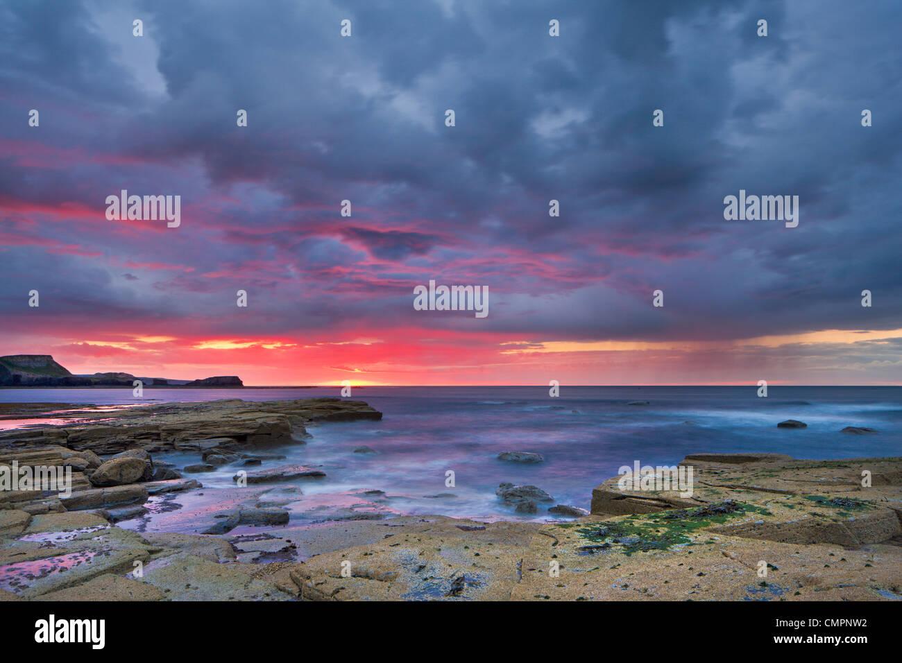 Coucher du soleil et nuages orageux à marée basse dans la baie d'Saltwick, Yorkshire, Angleterre, Photo Stock