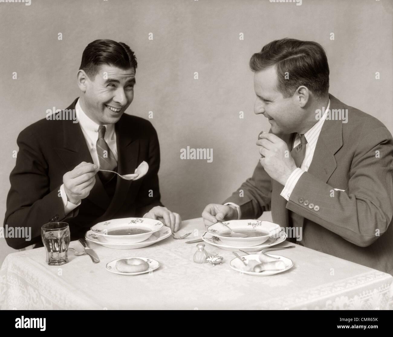 Années 30, deux hommes salle manger la soupe SMILING Photo Stock
