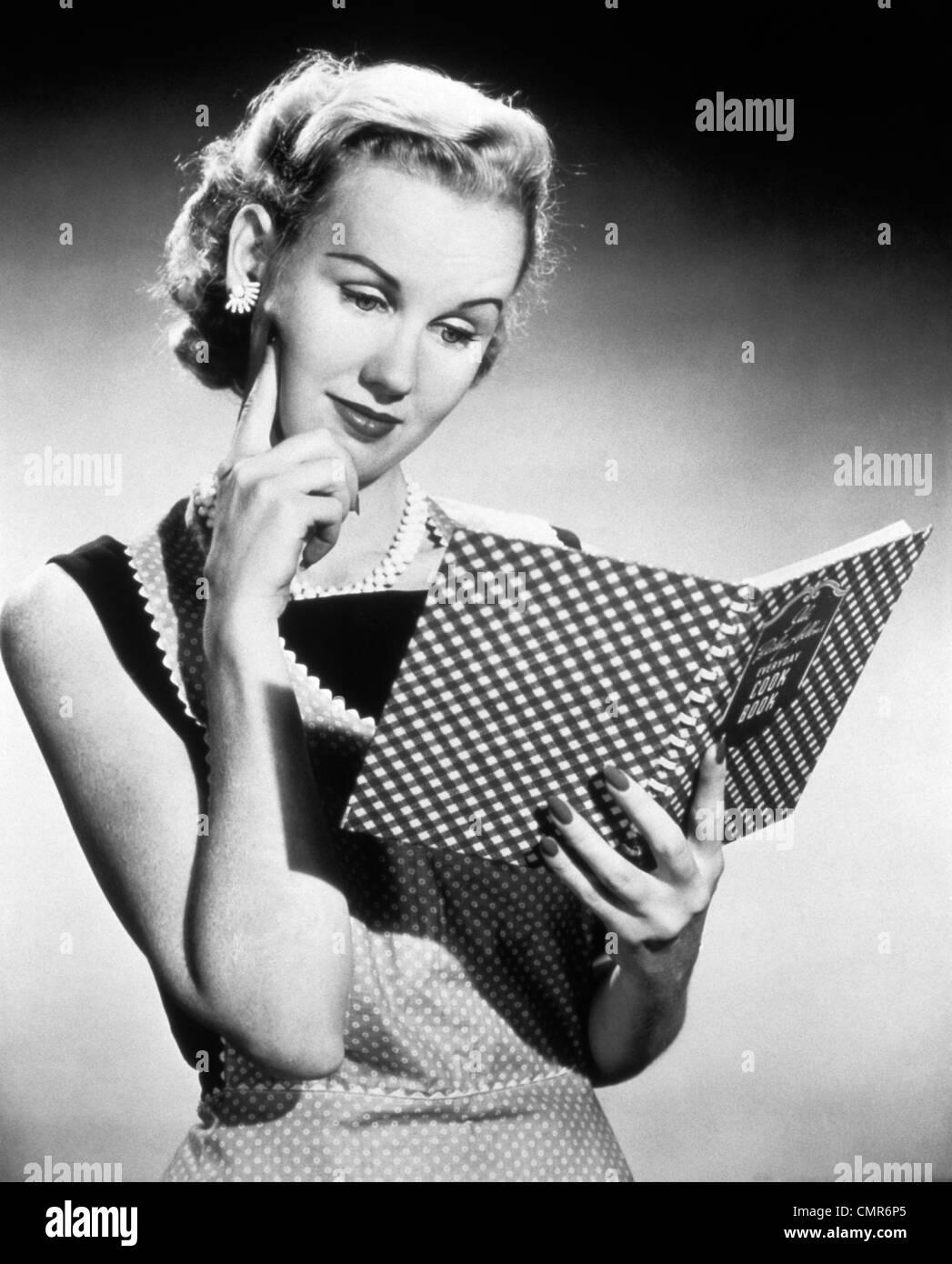 1950 FEMME AU FOYER BLONDE RÉFLÉCHIE LA LECTURE DE LIVRE de cuisinier Photo Stock