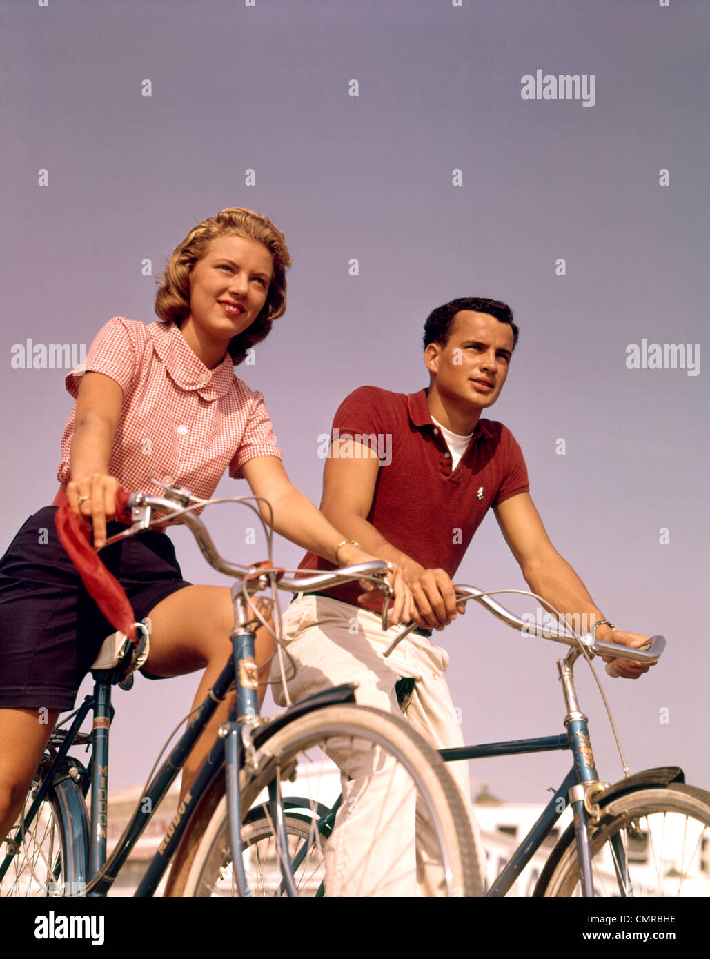 Années 1950 Années 1960 HOMME FEMME COUPLE Riding BICYCLES OUTDOORS Photo Stock