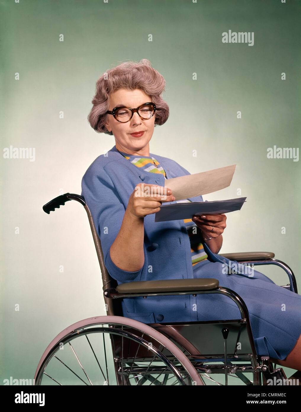1960 SENIOR WOMAN WEARING GLASSES SITTING IN WHEELCHAIR READING PATIENT SOINS DE CHÈQUE D'ASSURANCE-lettre Photo Stock