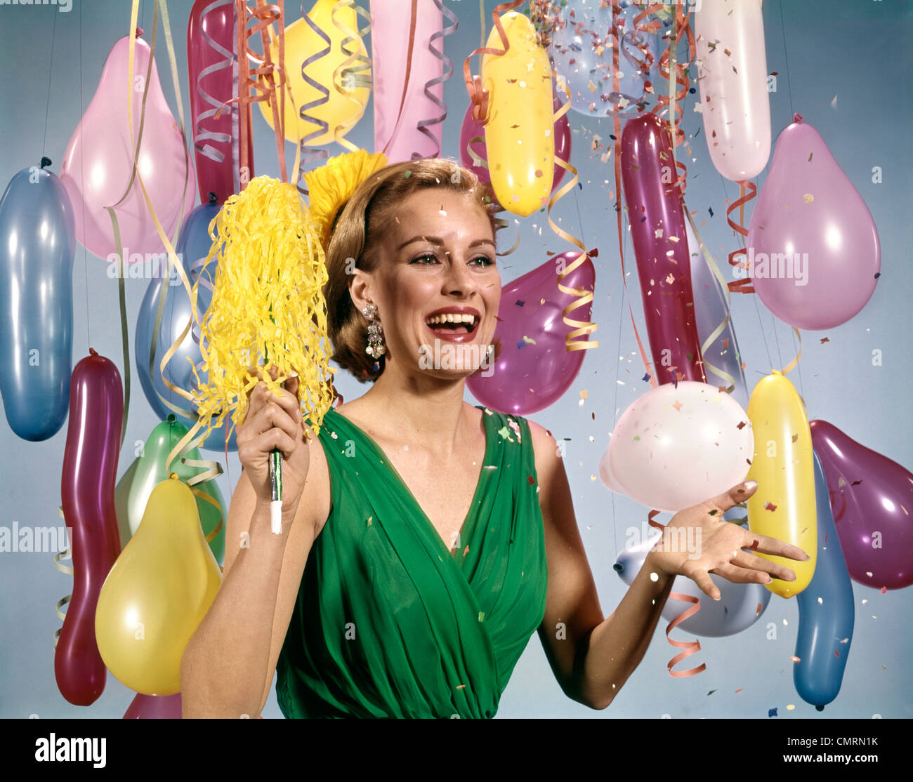 1960 1960 RETRO PARTY NOUVEL AN FEMME ROBE BALLONS BANDEROLES HEUREUX Photo Stock