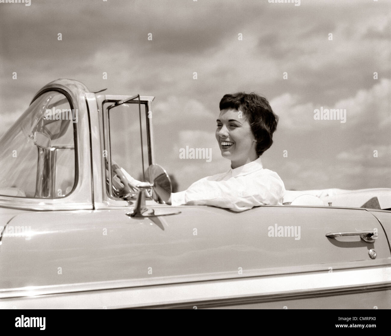 1950 SMILING WOMAN DRIVING AUTOMOBILE cabriolet Chevrolet Photo Stock