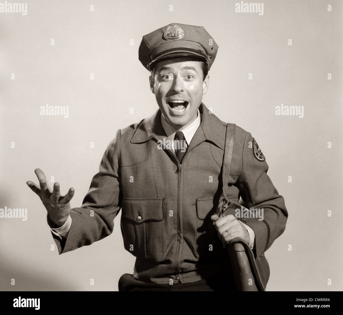 1960 STUDIO PORTRAIT OF HAPPY MAN POSTMAN MAILMAN LOOKING AT CAMERA Photo Stock