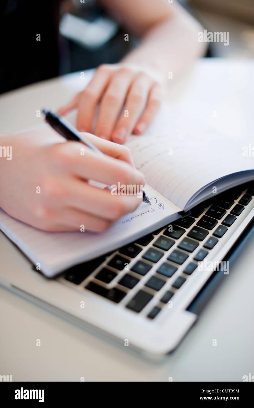 Femme écrit dans le bloc-notes tout en le maintenant sur le clavier Photo Stock