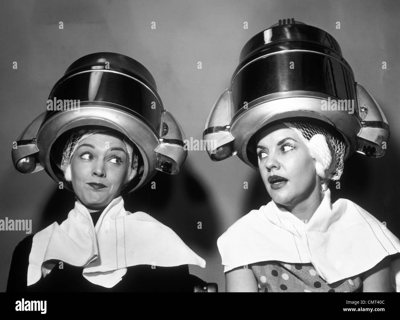 Années 50, deux femmes siégeant ensemble COMMÉRAGE SOUS COIFFURE Sèche cheveux Photo Stock
