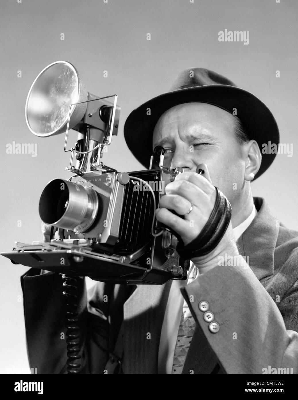 1950 PORTRAIT DE PHOTOGRAPHE MAN IN SUIT ET FEDORA HAT en plissant les yeux pour regarder à travers le viseur Photo Stock