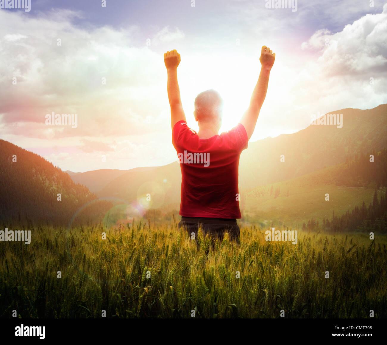 Jeune homme avec bras levés à la recherche au coucher du soleil avec les montagnes de l'avant Photo Stock
