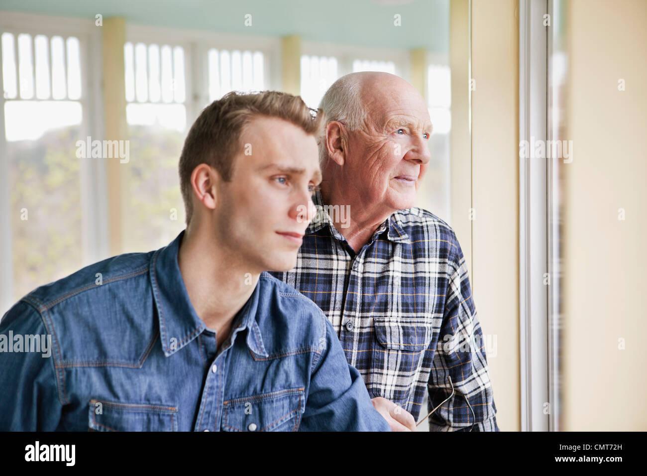 Personnes âgées et plus jeune homme à la fenêtre par l'intermédiaire de Photo Stock