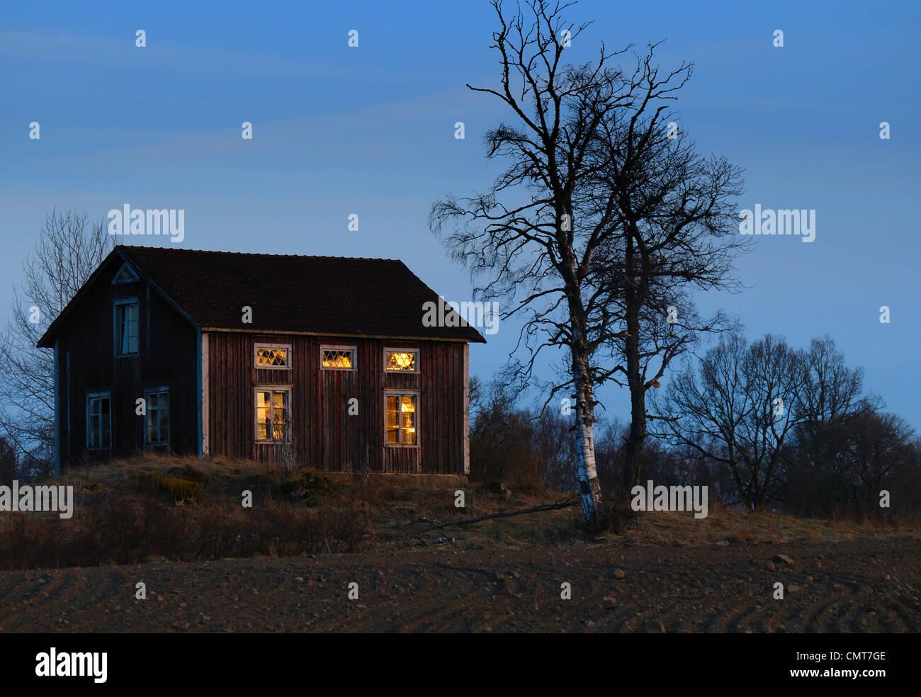 Extérieur de maison avec la lumière dans les fenêtres Photo Stock