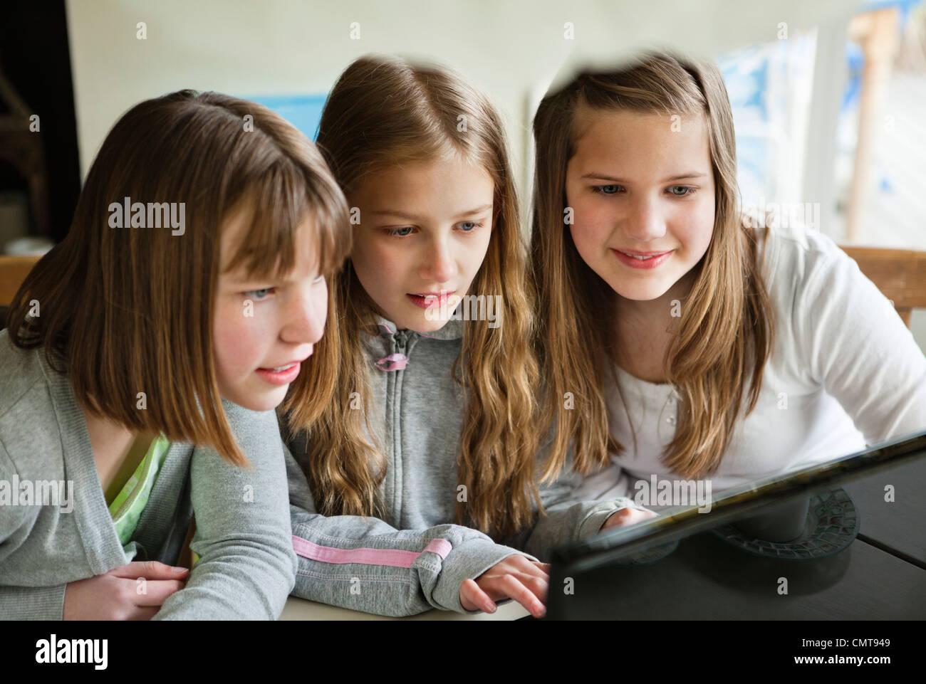 Smiling friends (12-13) à l'aide d'ordinateur Photo Stock