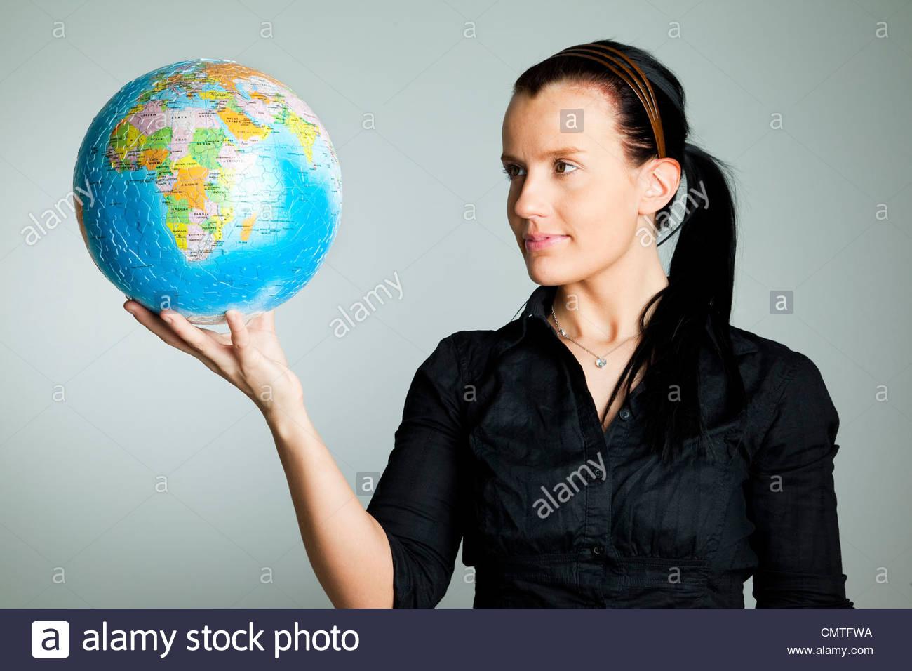 Femme debout avec globe terrestre dans sa main Photo Stock