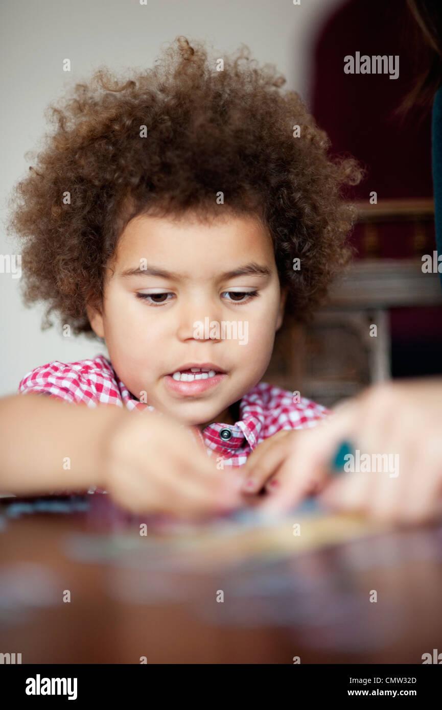 Fille d'âge préscolaire remplissant Jigsaw Puzzle Photo Stock