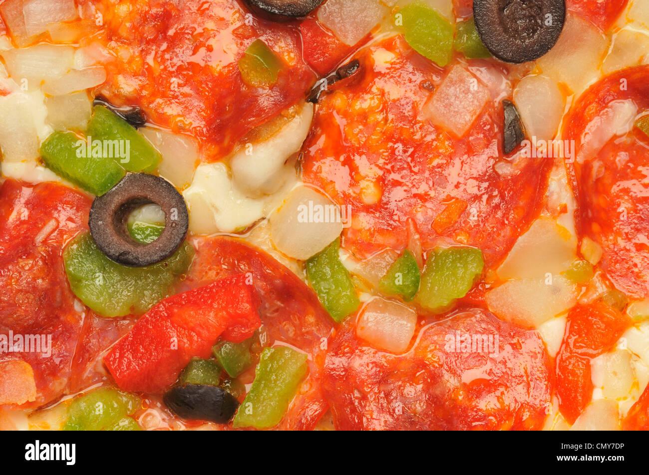 Détail Macro close-up de pizza au fromage, pepperoni, poivrons rouges et verts, oignons et olives noires Banque D'Images