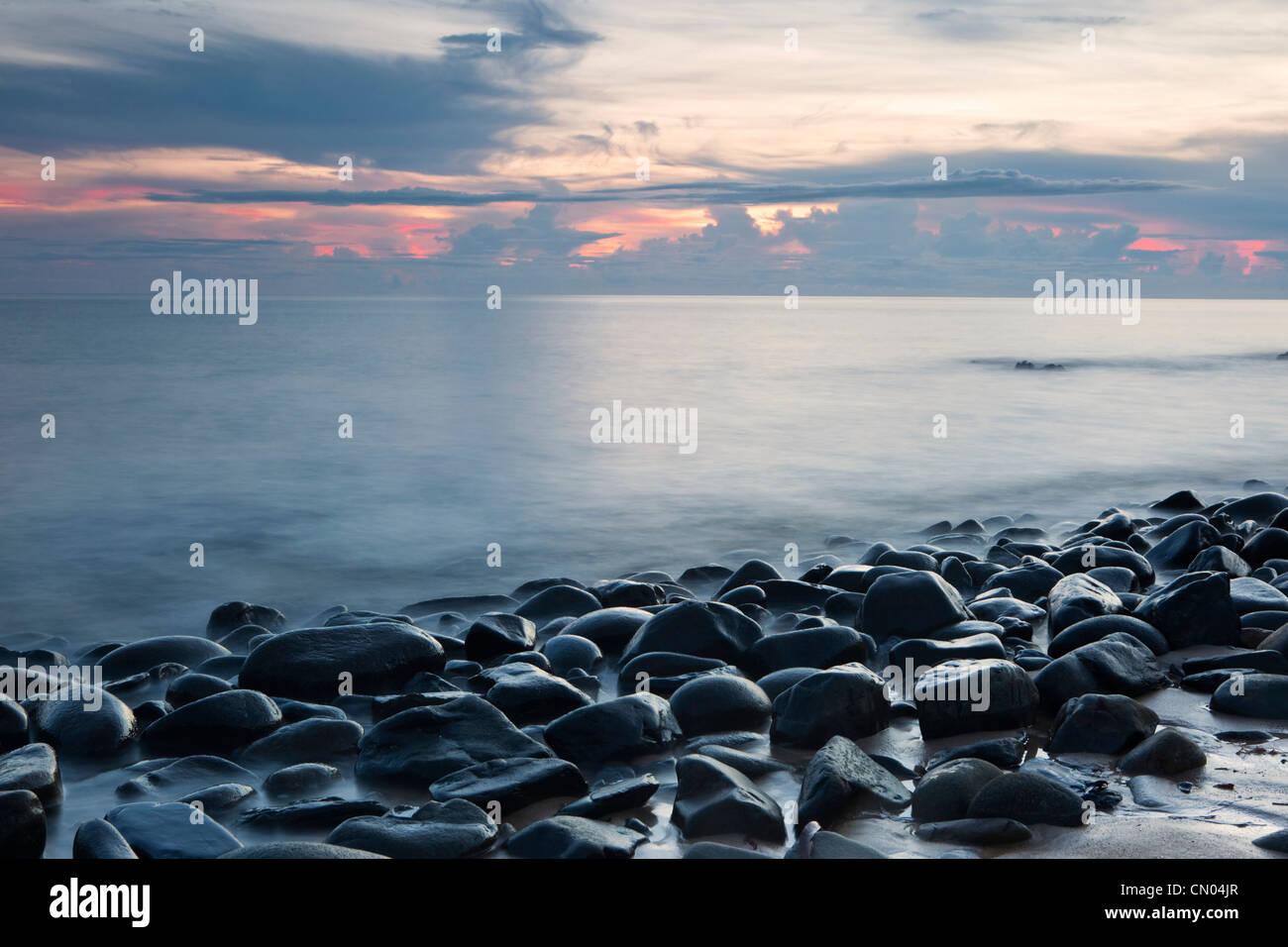 Clapotis des vagues des pierres sur une plage de galets à l'aube, près de Cairns, Queensland, Australie Photo Stock