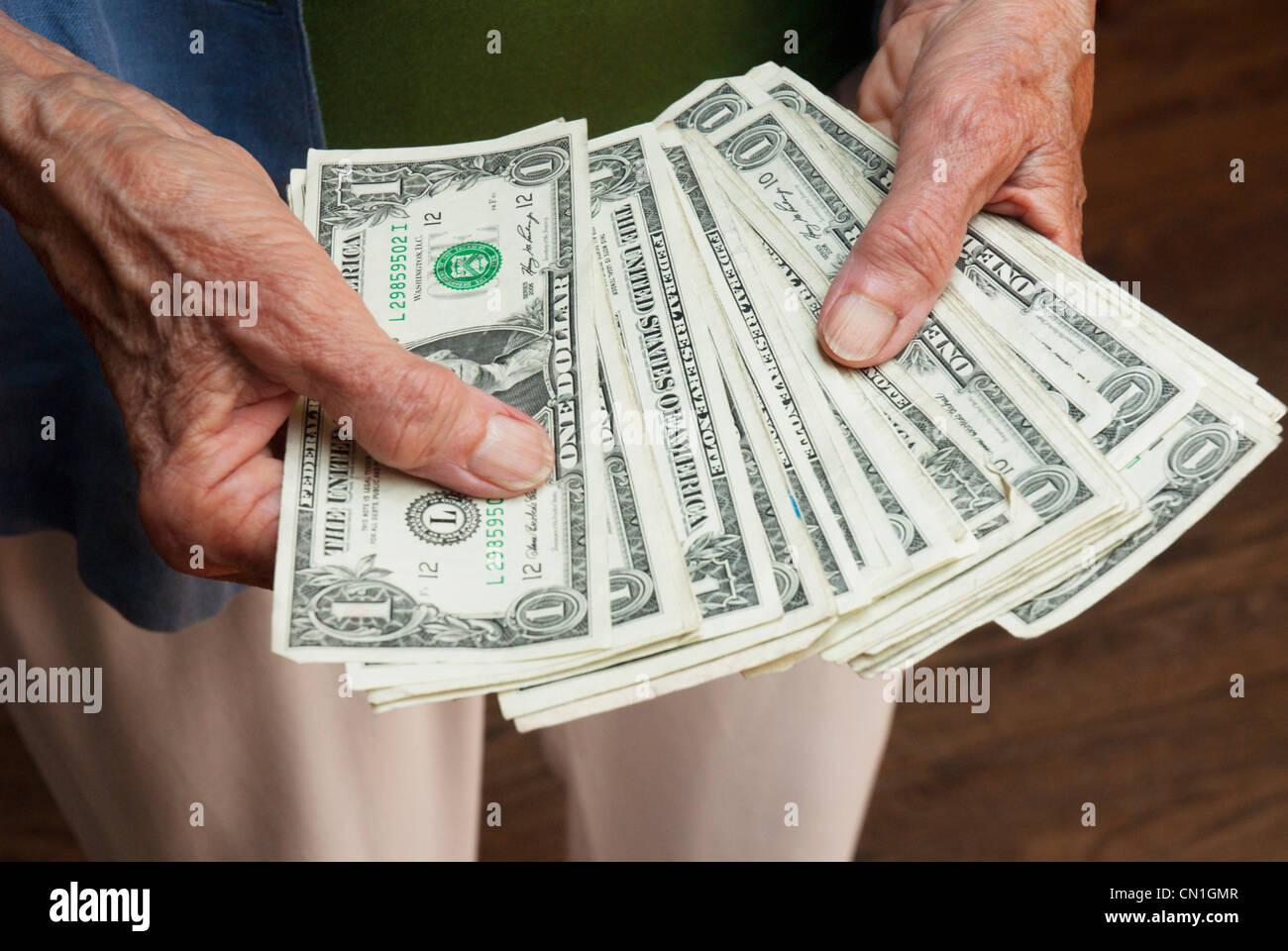 Older Woman's Hands Holding Dollar Bills Photo Stock