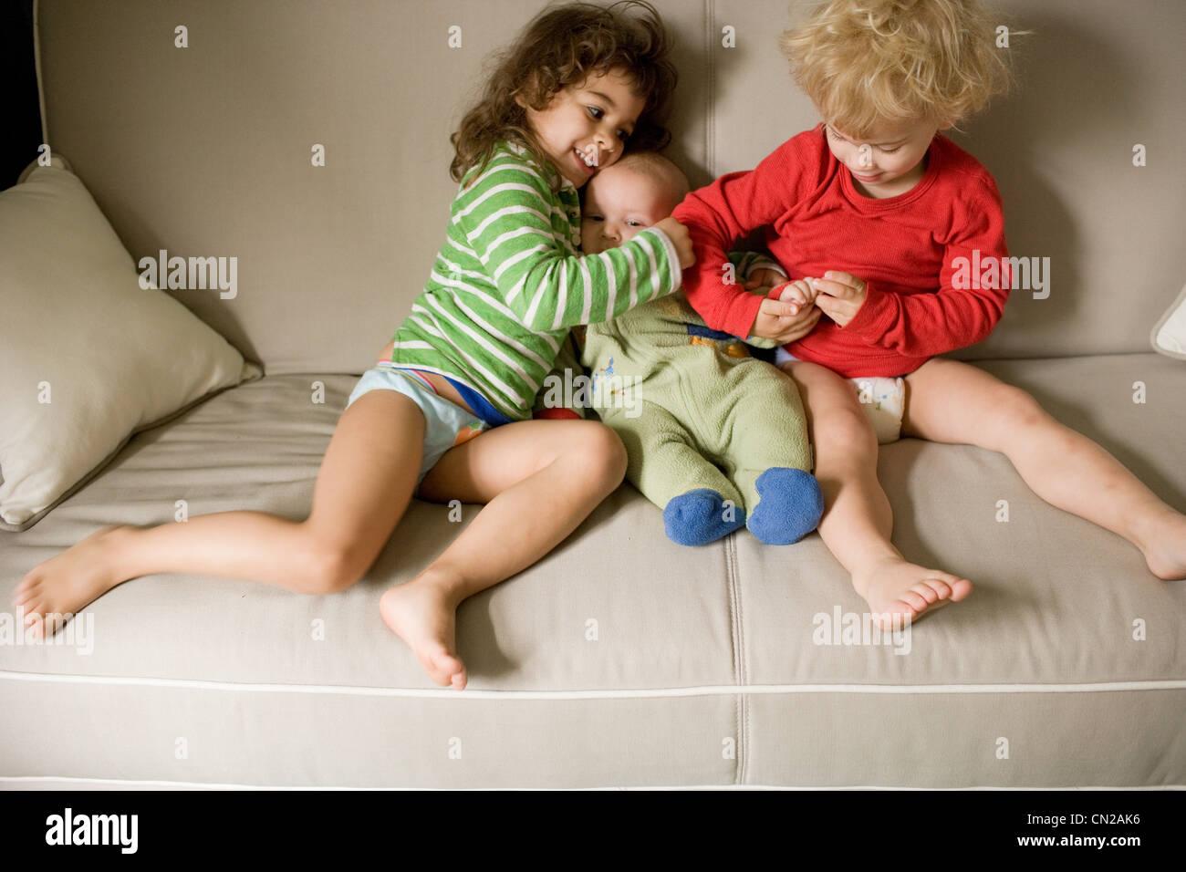 Trois frères sitting on sofa Photo Stock