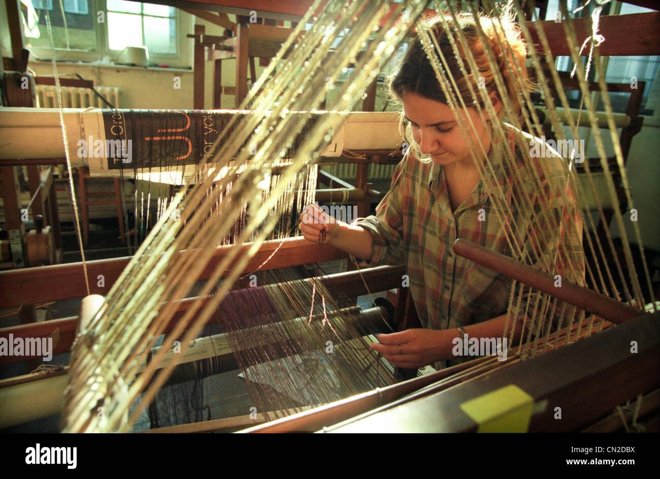 Une université de Brighton étudiant textile inspecte le fils de laine sur un métier dans le cadre Photo Stock