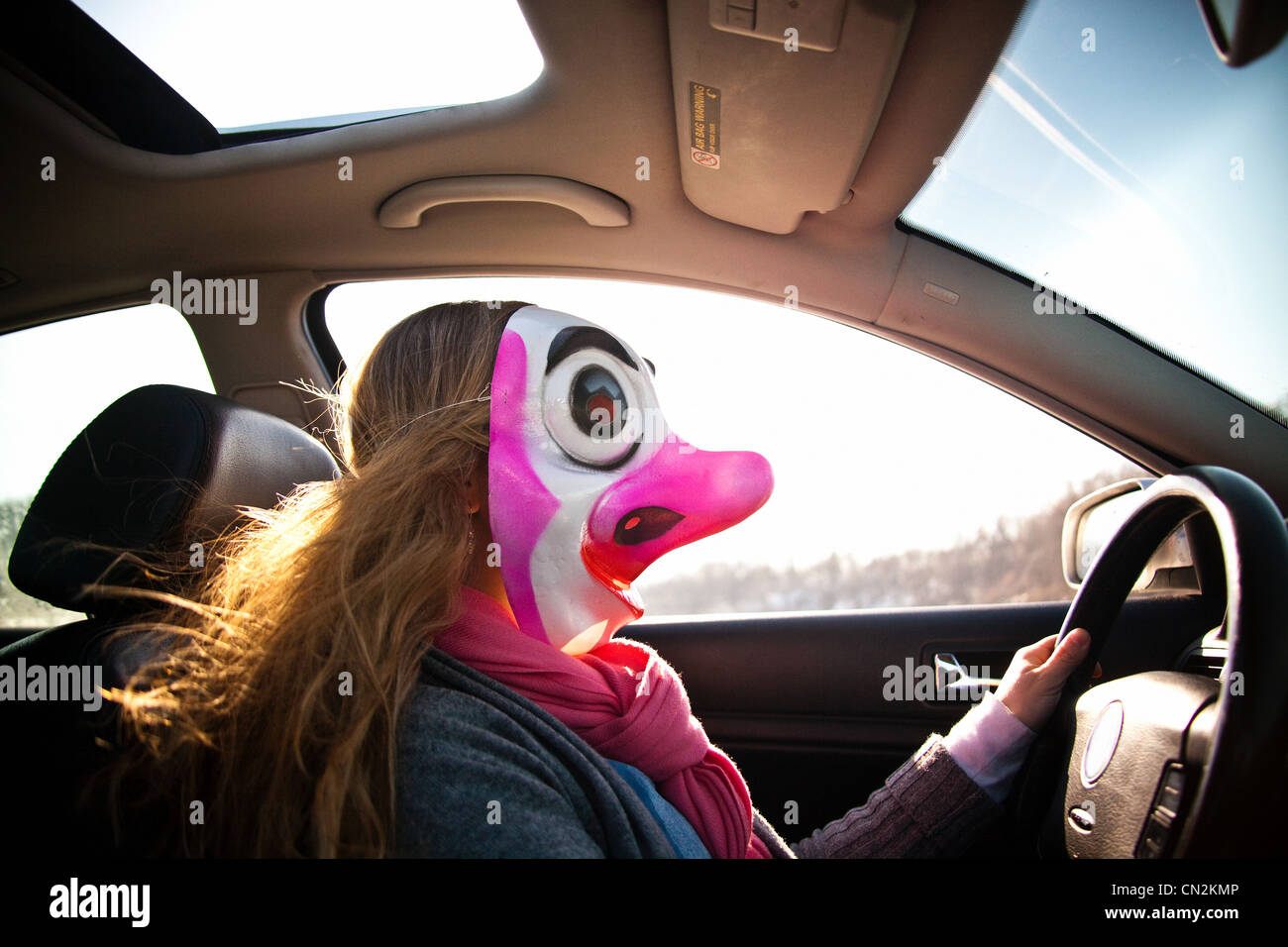 Femme au volant voiture portant un masque de clown Photo Stock