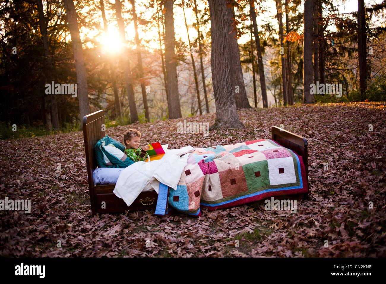 Jeune garçon au lit dans la forêt Photo Stock