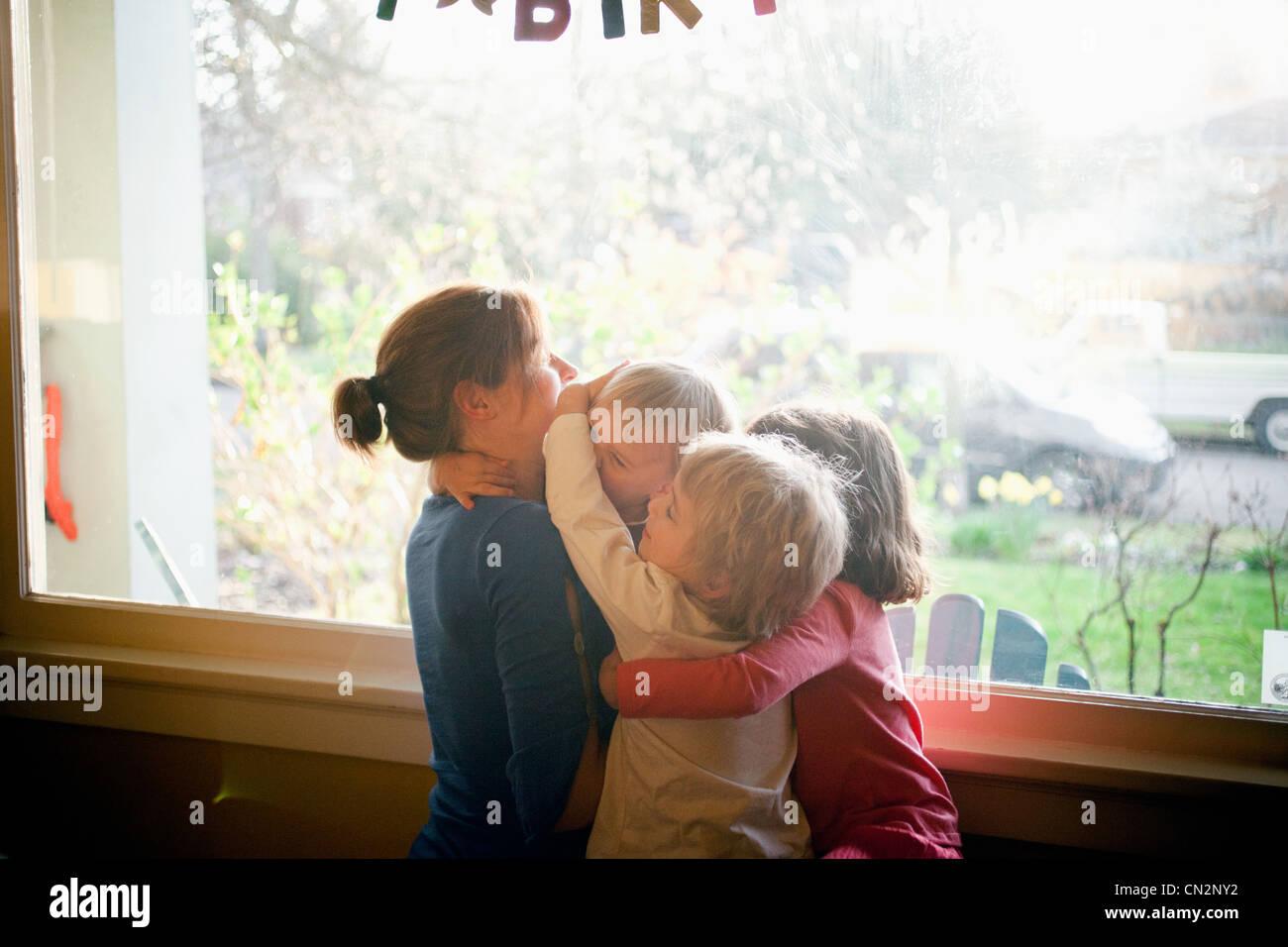 Mère embrassant trois enfants Photo Stock