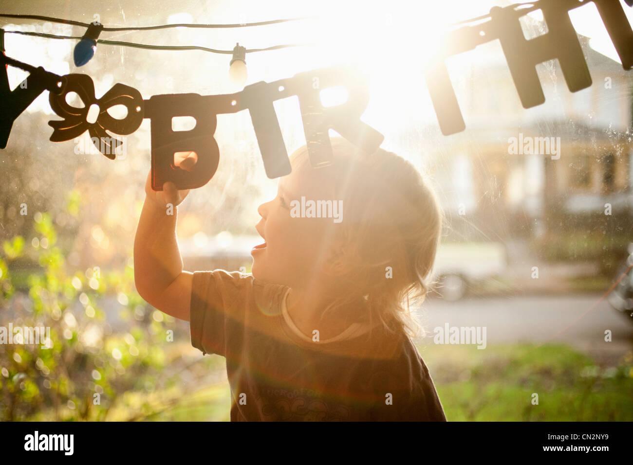 Jeune garçon toucher bannière anniversaire Photo Stock
